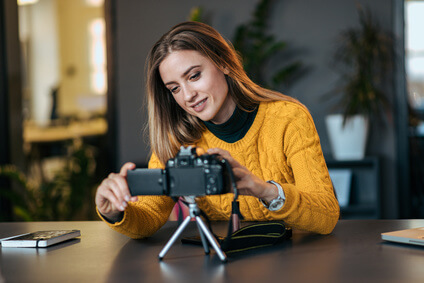 Young woman preparing camera for vlogging.